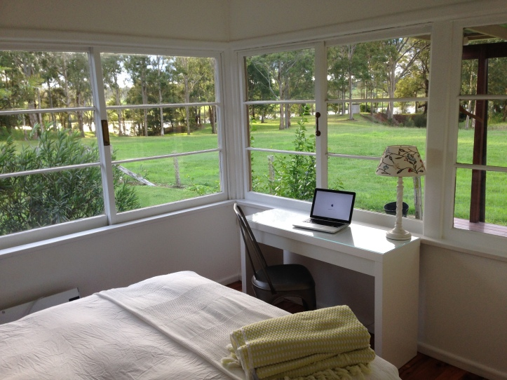 Writing retreat bedroom with desk, view of river