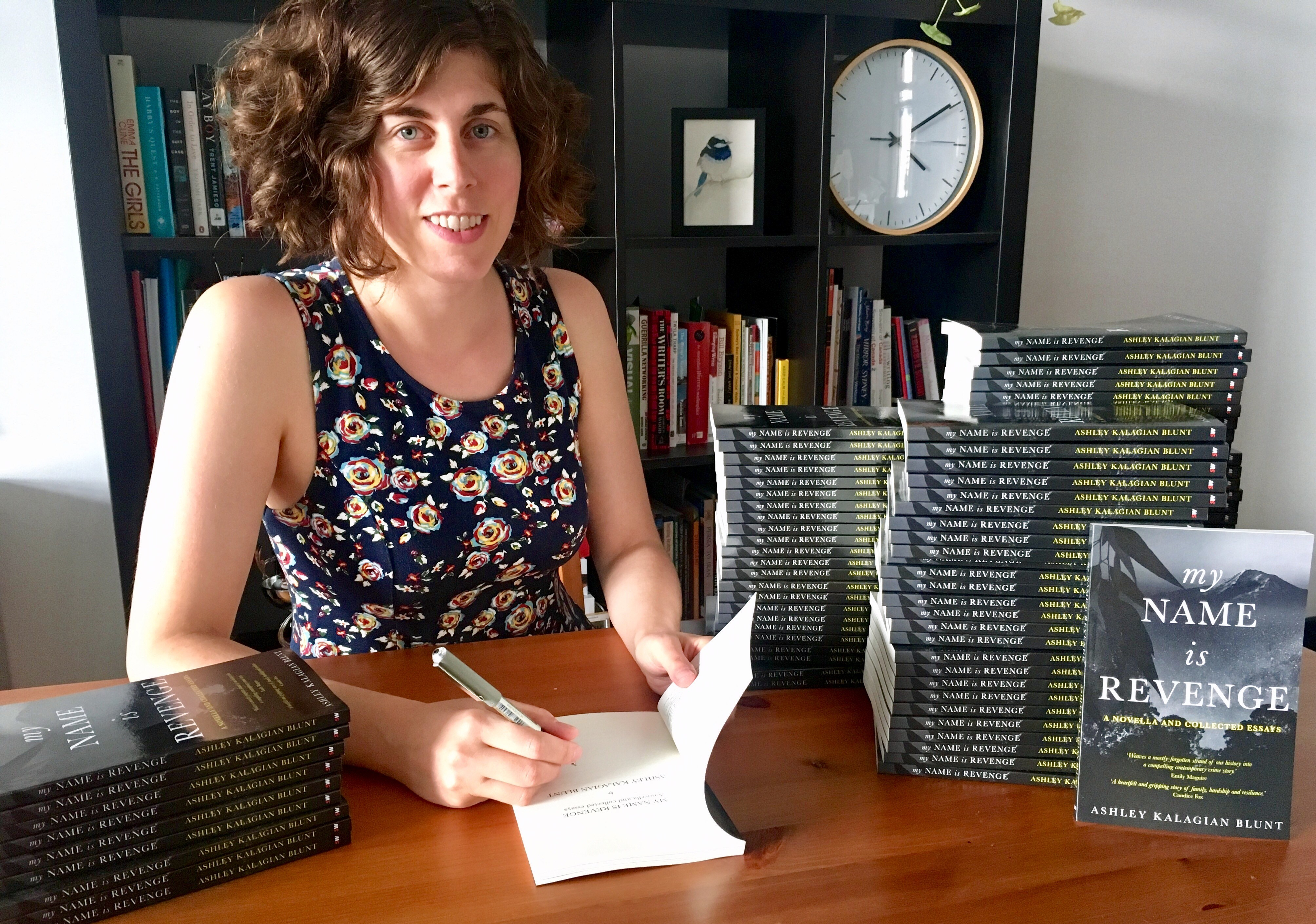 Author with stacks of books, My Name Is Revenge