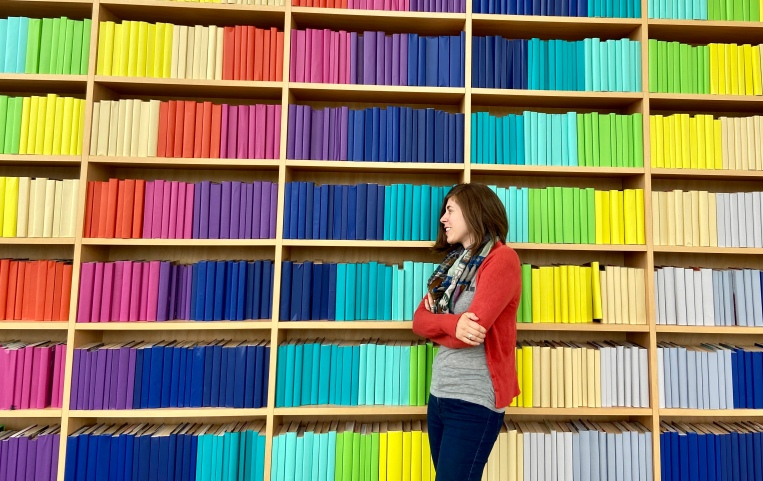 Author Ashley Kalagian Blunt with rainbow bookshelves