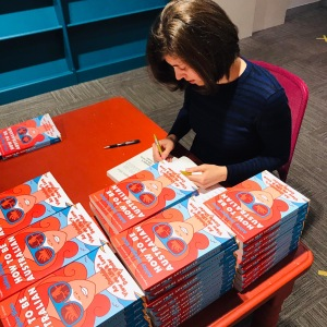 Author signs stacks of book