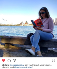 Woman reads book in front of Sydney Opera House, water