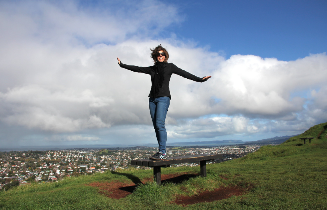 Woman stands on hilltop bench above Auckland
