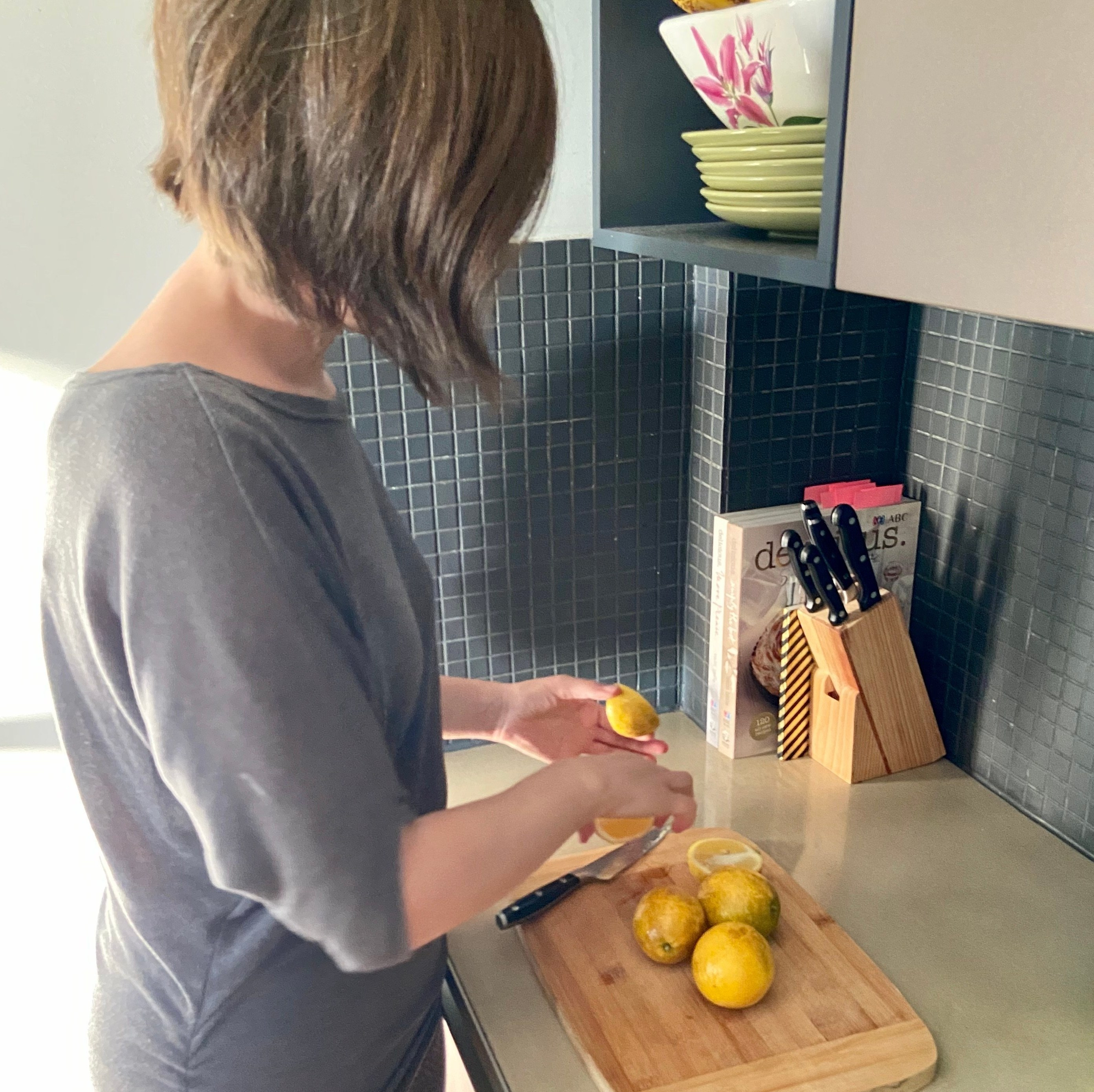 Woman cuts lemonades in kitchen