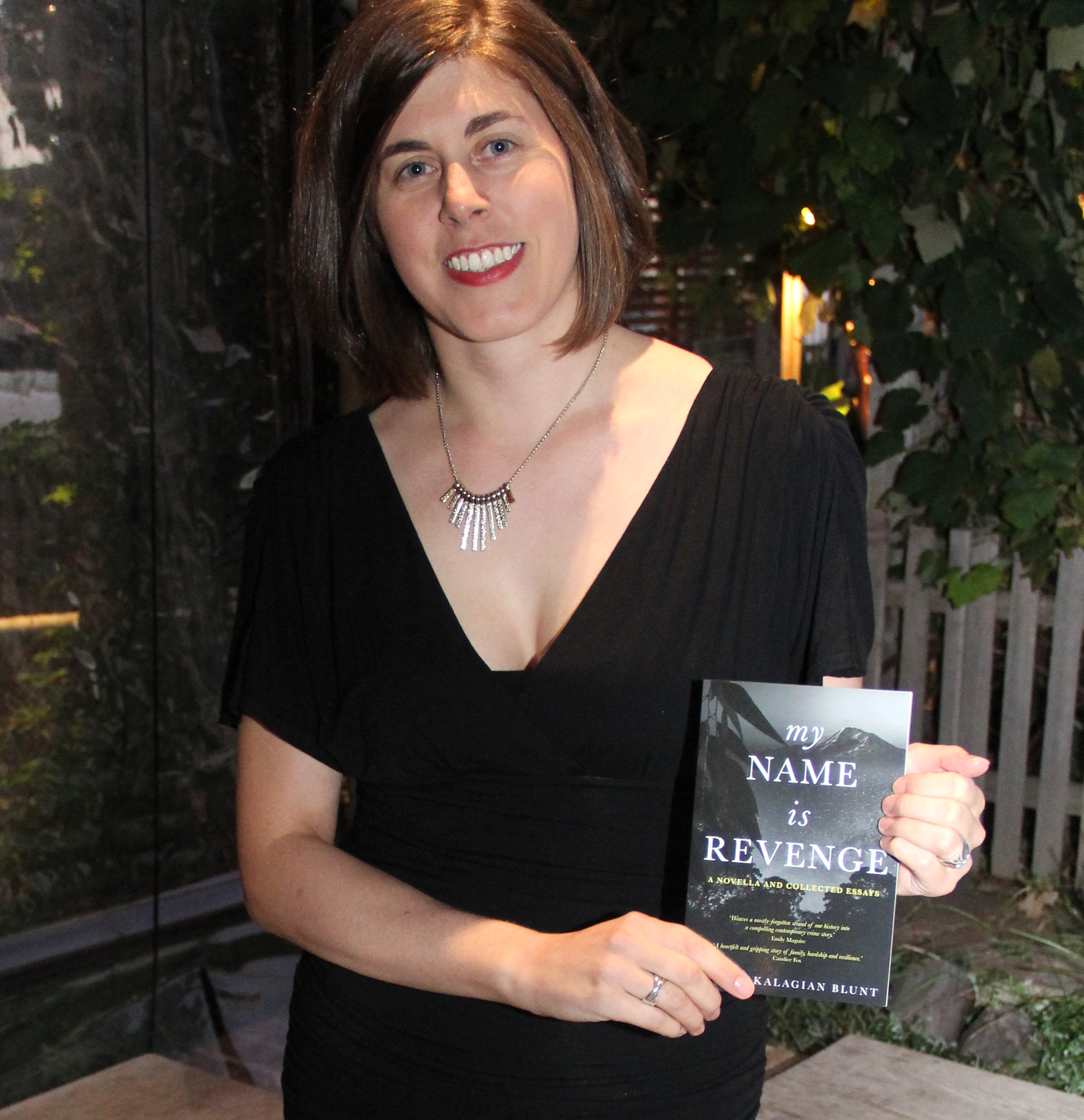 Young female author holding book titled My Name Is Revenge